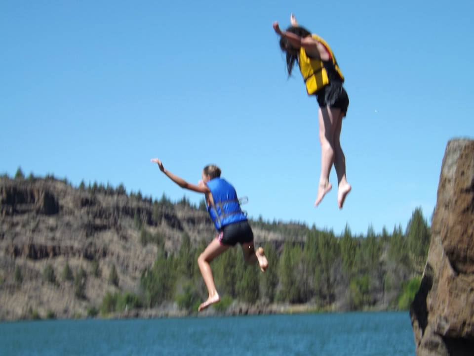 Two girls jumping off roacks.